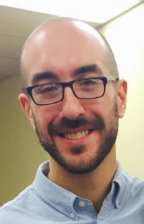 Headshot of Dan smiling. He is wearing a light blue collared shirt, black box-frame glasses, and a shiny, shiny bald head.